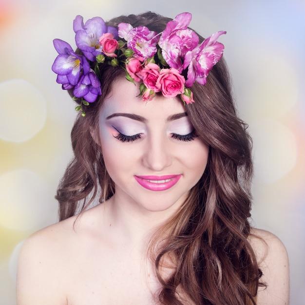 Hermosa niña sonriente con flores en el pelo Foto Premium