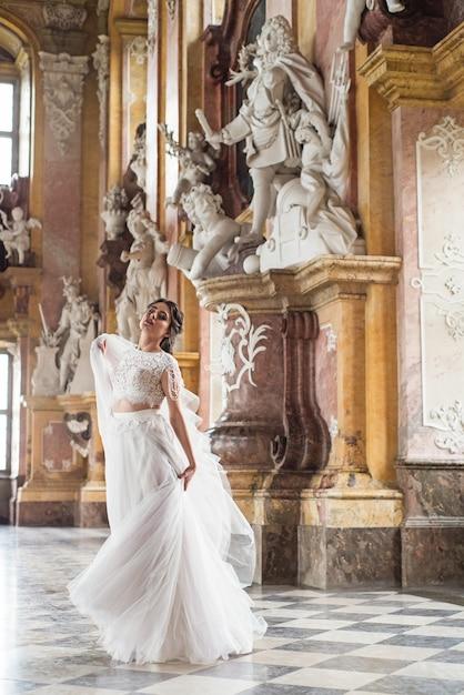 Hermosa novia en el interior de lujo barroco castel. Foto Premium