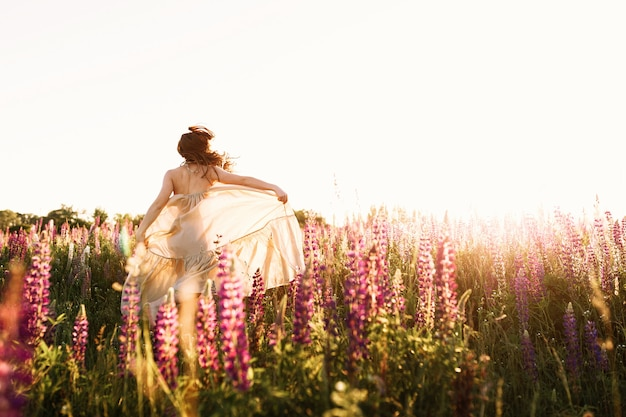 Una hermosa novia en traje de novia está bailando sola en un campo de trigo. Foto gratis