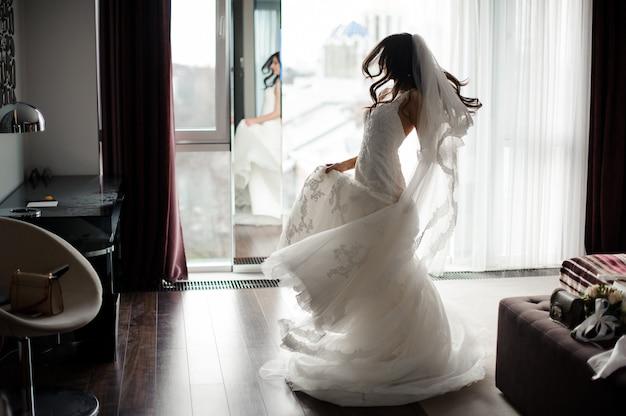 Hermosa novia con vestido blanco y velo bailando cerca de la ventana Foto Premium
