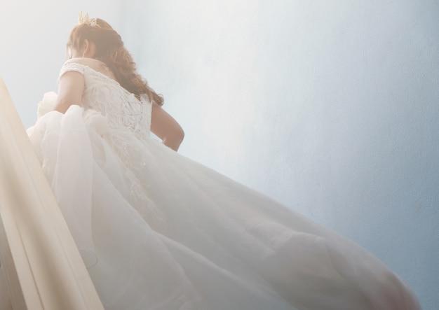 hermosa novia en vestido de novia blanco caminando por las escaleras