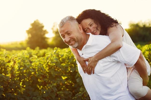 Hermosa pareja adulta pasa tiempo en un campo de verano Foto gratis