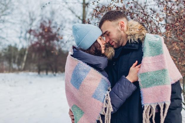 Hermosa pareja amorosa caminando y abrazándose en el bosque de invierno. calentamiento de personas cubierto con una manta Foto Premium
