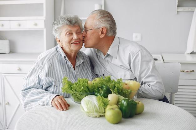 Hermosa pareja de ancianos prepara la comida en la cocina Foto gratis