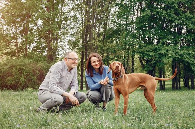 Hermosa pareja en un bosque de verano con perros Foto gratis