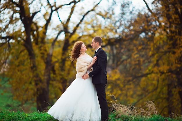 Hermosa pareja disfrutando el abrazo el uno del otro y tiernamente sonriendo Foto Premium