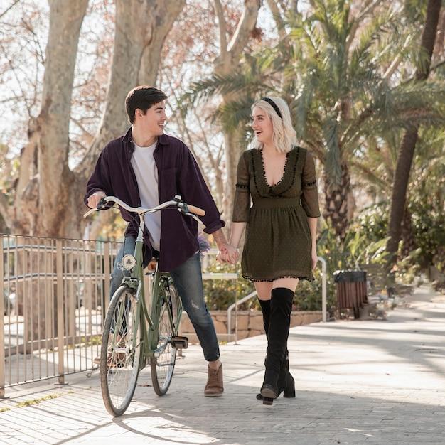 Hermosa pareja en el parque con bicicleta Foto gratis