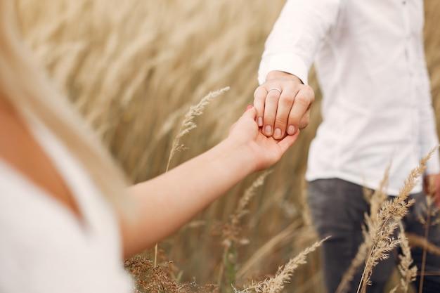 Hermosa pareja pasa tiempo en un campo de otoño Foto gratis