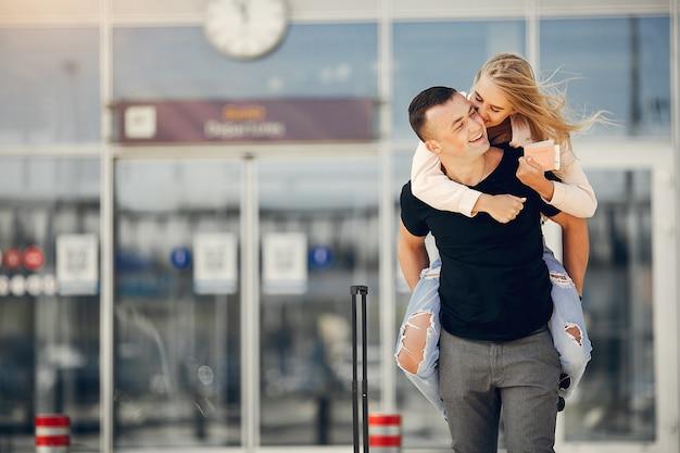 Hermosa pareja de pie en el aeropuerto Foto gratis