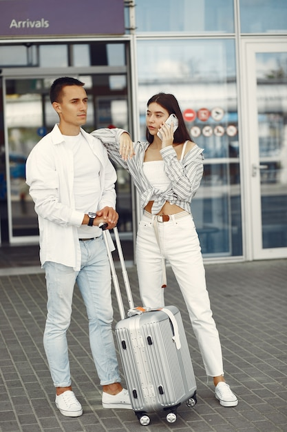 Hermosa pareja de pie cerca del aeropuerto Foto gratis