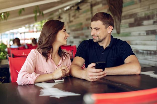 Hermosa pareja sentada en un café de verano Foto gratis