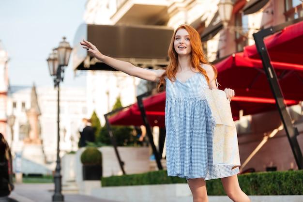 Hermosa pelirroja en vestido sosteniendo un mapa de la guía de la ciudad Foto gratis