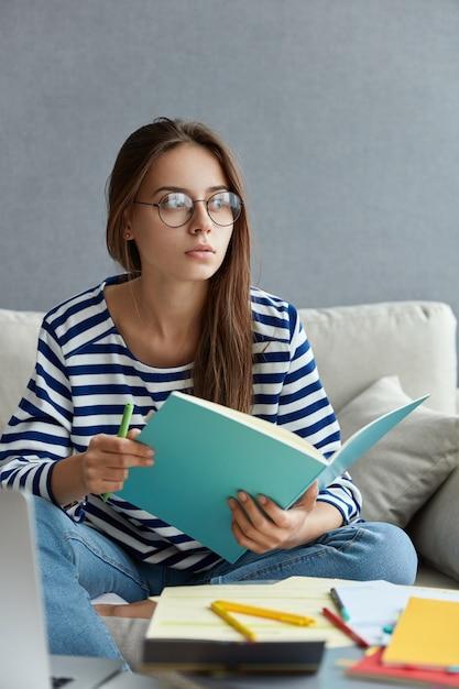 Hermosa periodista reflexiva sostiene un cuaderno y un bolígrafo azul, escribe un artículo, usa gafas redondas transparentes, se sienta en el sofá en casa Foto gratis