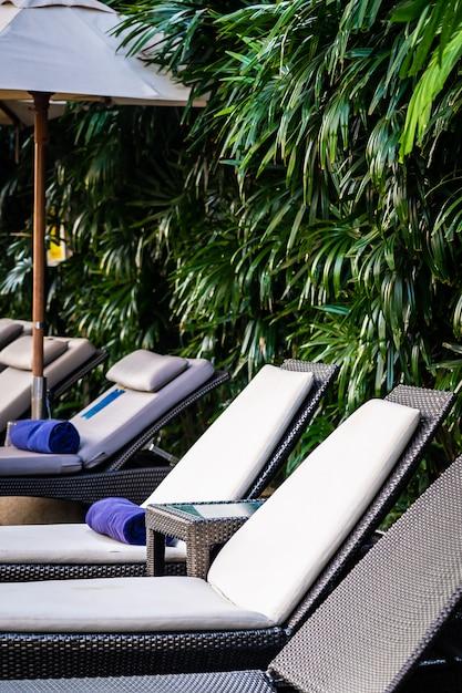 Hermosa piscina al aire libre con tumbona y sombrilla en el resort para viajes y vacaciones Foto gratis