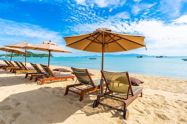 Hermosa playa tropical mar y océano con palmera de coco y sombrilla y silla en cielo azul Foto gratis