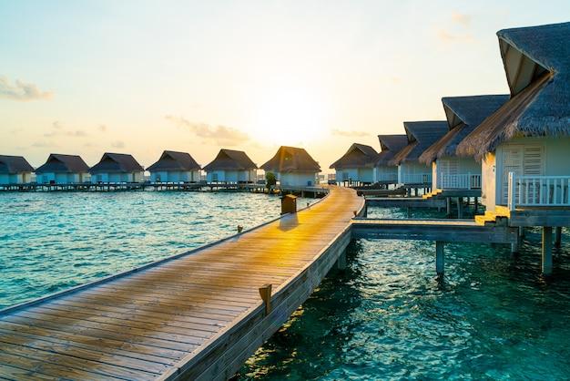 Hermosa puesta de sol tropical sobre la isla de maldivas con bungalow de agua en hotel resort Foto Premium