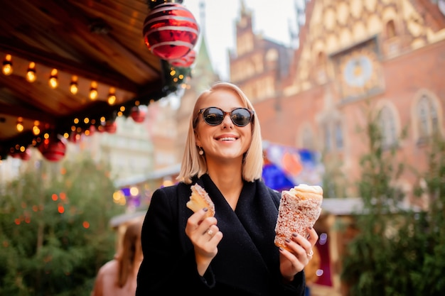 Hermosa rubia con pastel de saliva en el mercado de navidad en wroclaw, polonia Foto Premium