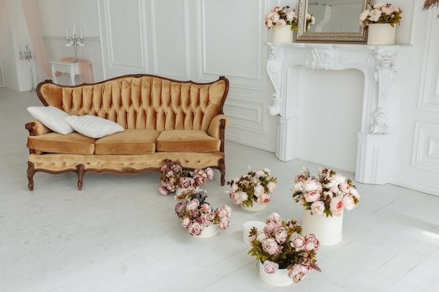 Hermosa sala de estar de provance con sofá marrón junto a la chimenea con flores y velas Foto gratis