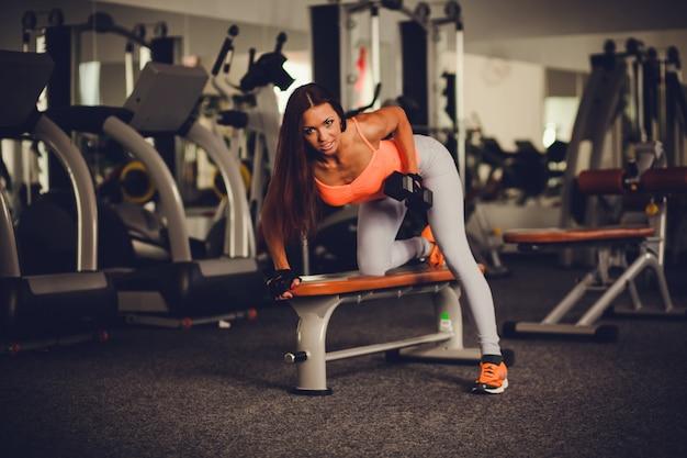 Hermosa y sexy mujer haciendo ejercicios con mancuernas. Foto Premium
