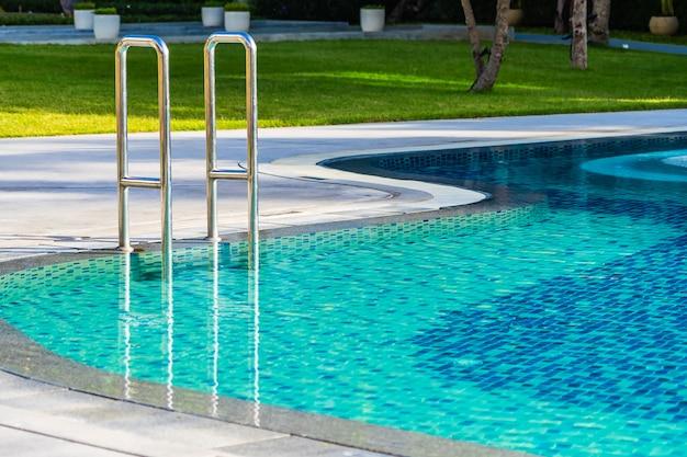 Hermosa sombrilla y silla alrededor de la piscina al aire libre en el complejo hotelero para viajes de vacaciones Foto gratis
