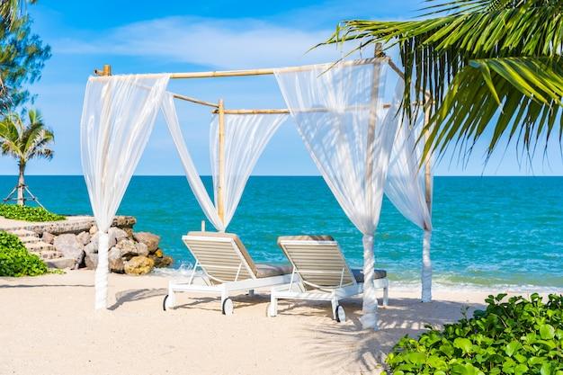 Hermosa sombrilla y silla alrededor de playa mar océano con cielo azul para viajar Foto gratis