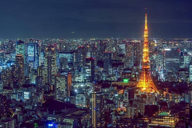 Hermosa toma aérea de la arquitectura moderna de la ciudad con una torre iluminada en el lateral Foto gratis