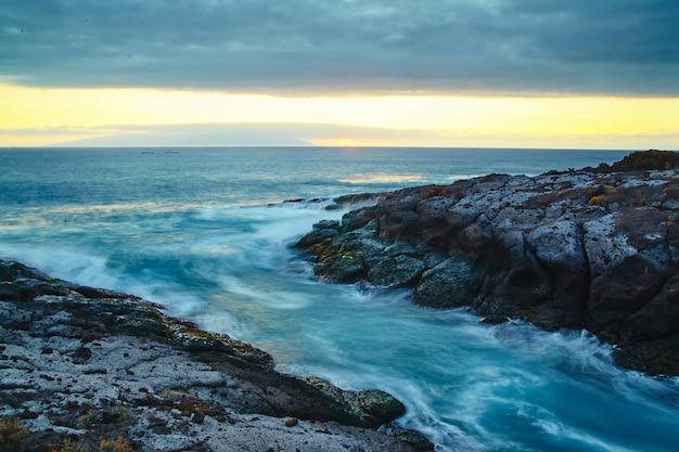 Hermosa vista desde el acantilado de la montaña hasta el océano con cielo azul y nubes Foto gratis