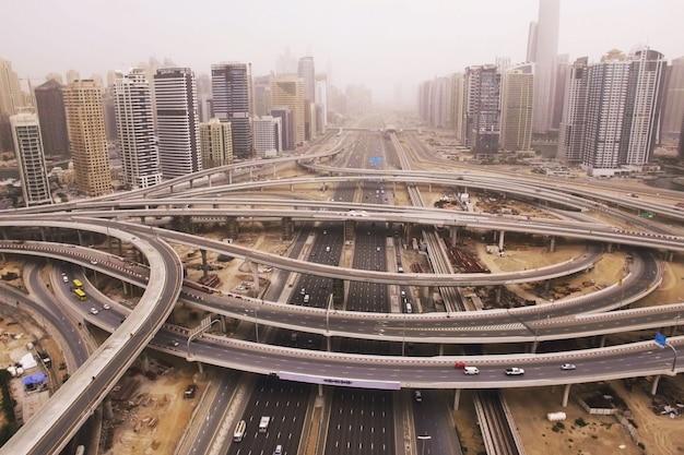 Hermosa vista aérea del paisaje futurista de la ciudad con carreteras, automóviles, trenes, rascacielos. dubai Foto Premium