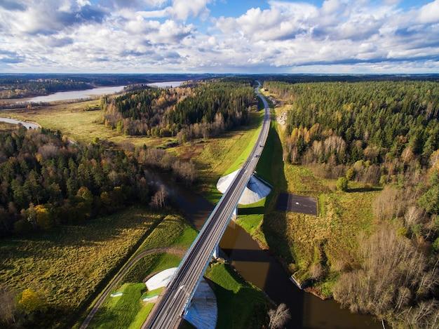 Hermosa vista aérea del puente de carretera sobre el río rodeado de bosque Foto Premium