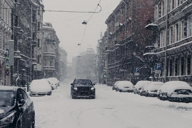 Hermosa vista de la maravillosa ciudad nevada con automóviles cubiertos de nieve Foto Premium