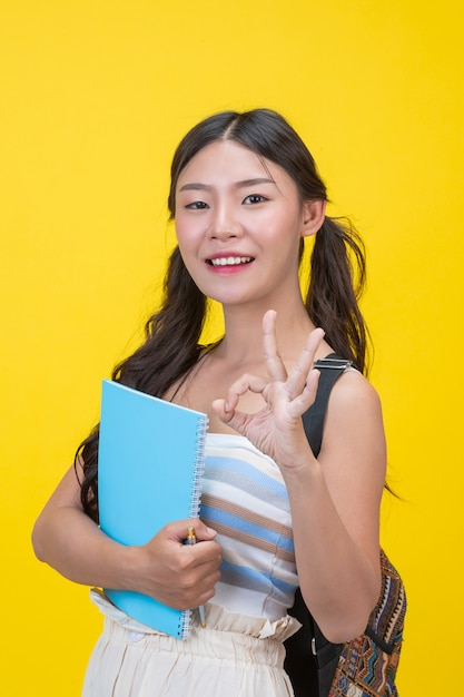 Hermosas alumnas sostienen cuadernos y bolígrafos Foto gratis