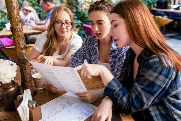 Hermosas chicas caucásicas están pidiendo especiales del menú en la terraza de una cafetería Foto gratis
