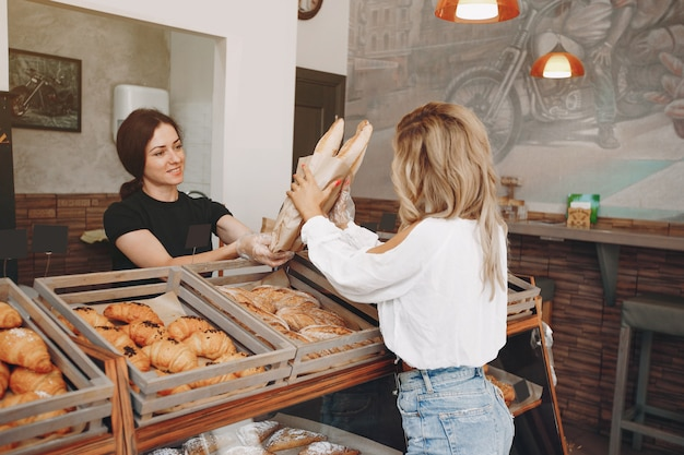Hermosas chicas compran bollos en la panadería Foto gratis