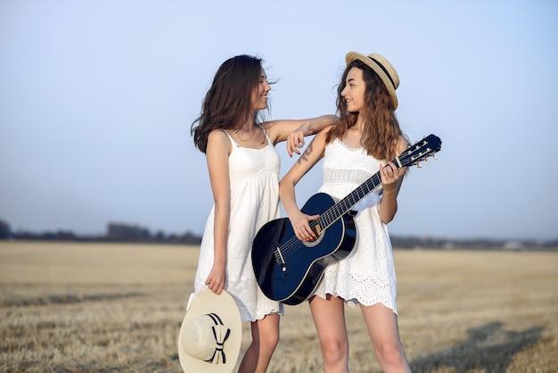Hermosas chicas elegantes en un campo de trigo de otoño Foto gratis