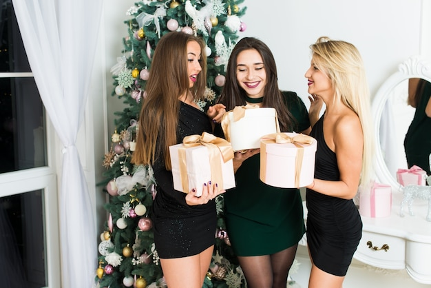 573a2e84af Hermosas chicas en navidad habitación decorada con cajas de regalo. navidad  y año nuevo concepto