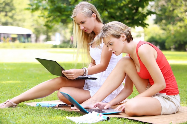 Hermosas chicas usando computadoras portátiles en un parque Foto gratis