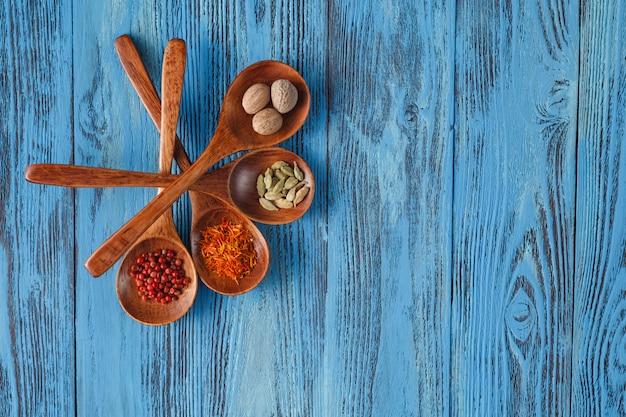 Hermosas especias coloridas en cucharas en una vieja mesa de madera azul. Foto Premium