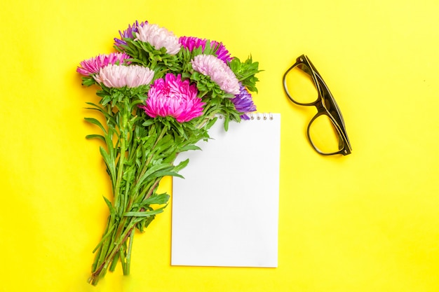 Hermosas flores de aster, bloc de notas blanco sobre fondo de color amarillo pastel Foto Premium