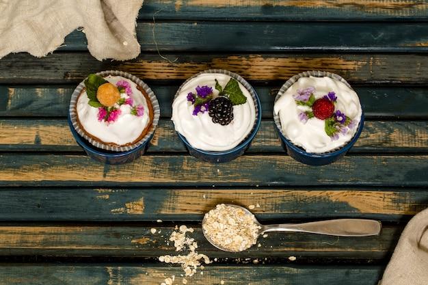 Hermosas magdalenas con frutos rojos sobre mesa de madera nueces miel Foto gratis