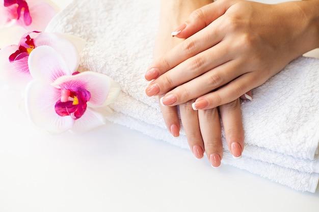 Hermosas uñas de mujer con manicura francesa, en estudio de belleza Foto Premium