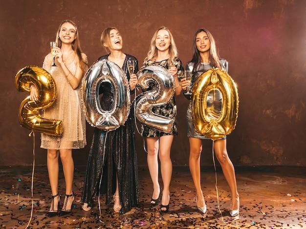 Hermosas mujeres celebrando el año nuevo. chicas hermosas felices en elegantes vestidos de fiesta sexy Foto gratis