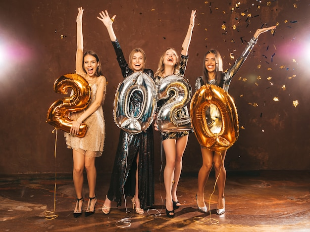 Hermosas mujeres celebrando año nuevo. niñas hermosas y felices con elegantes vestidos de fiesta sexys con globos dorados y plateados 2020, divirtiéndose en la fiesta de fin de año. celebración navideña levantando las manos Foto gratis