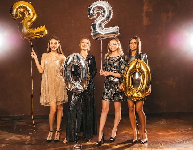 Hermosas mujeres celebrando año nuevo. niñas hermosas y felices con elegantes vestidos de fiesta sexys con globos dorados y plateados 2020, divirtiéndose en la fiesta de fin de año. celebración navideña modelos encantadores Foto gratis