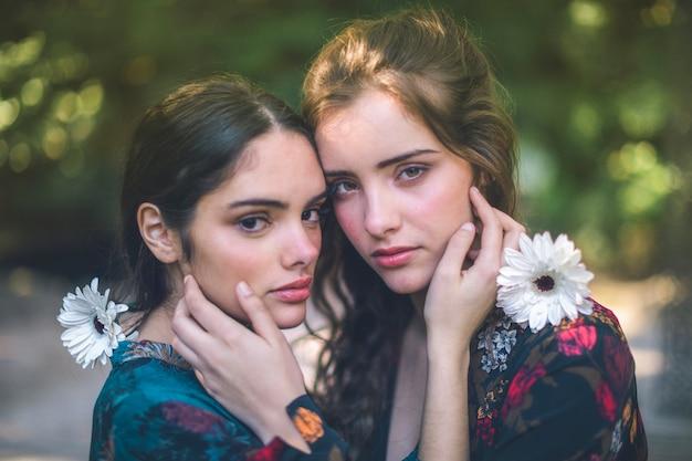 Hermosas mujeres sosteniendo flores y abrazos Foto gratis