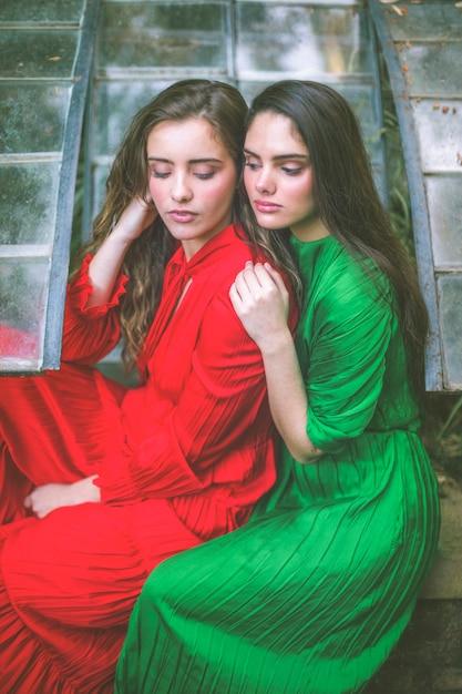 Hermosas mujeres en vestidos mirando hacia abajo Foto gratis