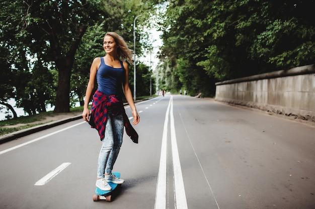 Hermosas rubias patines en el parque Foto gratis