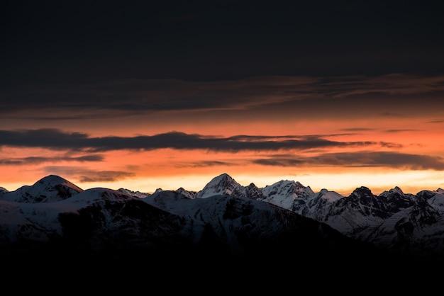 Hermoso amanecer en el horizonte con altas montañas y colinas nevadas y un cielo oscuro increíble Foto gratis