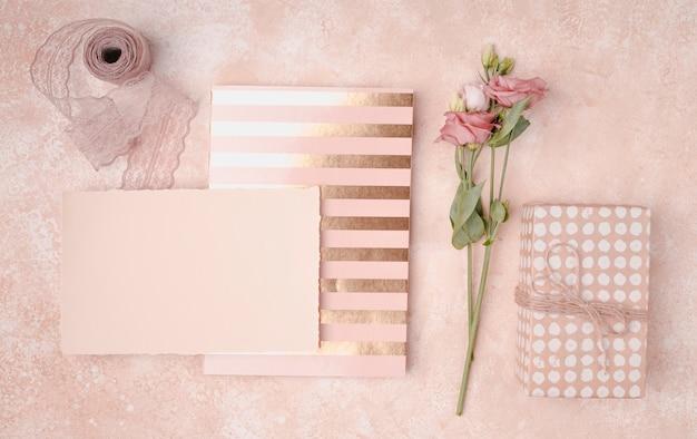 Hermoso arreglo con invitaciones de boda y flores. Foto gratis