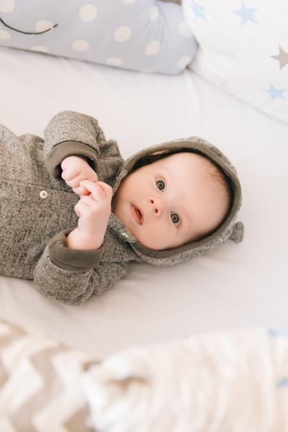 Hermoso Bebé Recién Nacido Acostado En Una Cama Ovalada Con Hermosos Parachoques En Delicados Tonos Grises Azules Y Blancos Foto Premium