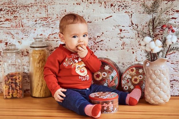 Hermoso bebé se sienta a la mesa y está comiendo una nuez Foto gratis